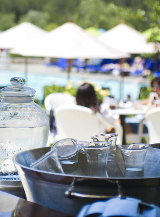 water carafes chilling in ice with pool in background.
