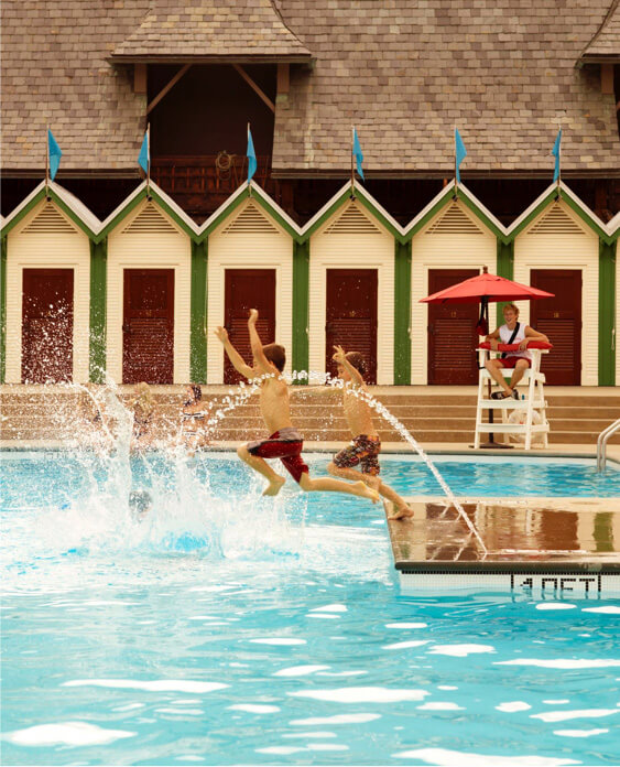 Children jumping into pool.