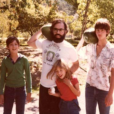 Francis Ford Coppola holding a watermelon, standing next to his children.