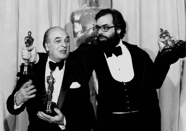 Francis Ford Coppola holding his Oscar awards.