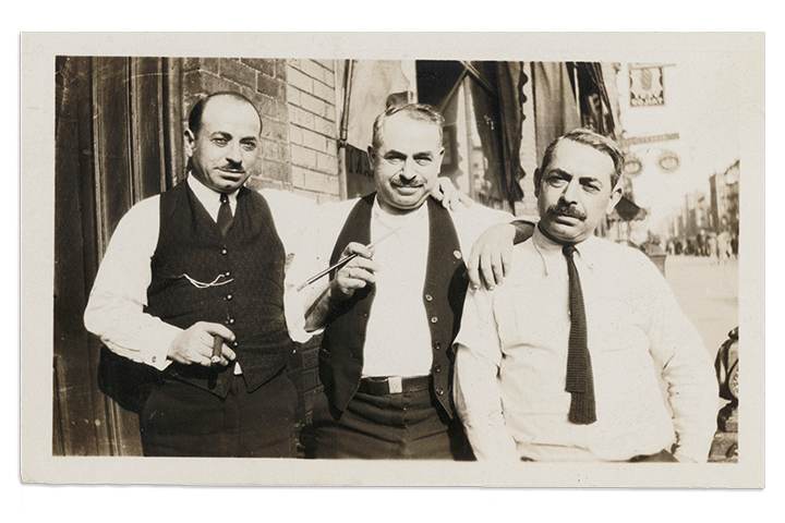 Black and white photo of three men standing on a street.
